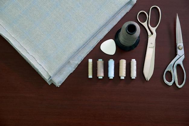 Группа шитья предметов, лежащих на деревянном столе, плоская планировка концепции ателье