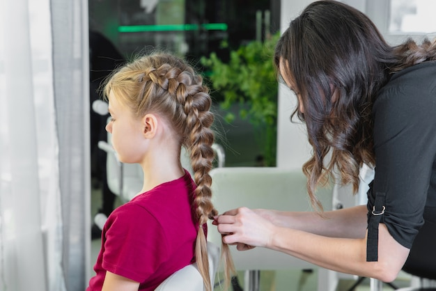 ヘアスタイリストが美容院でプレティーンの女の子に三つ編みを織る