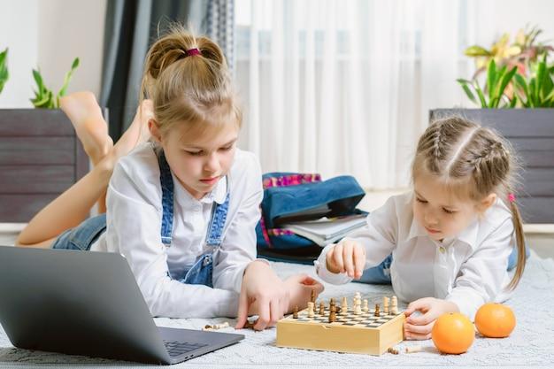 Две красивые маленькие сестры играют в шахматы на полу в гостиной
