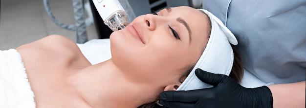 美容クリニックでレーザー治療を受ける若い女性