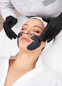カーボンピールのための美しい女性の顔に黒いマスクを適用する美容師
