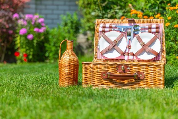 公園の緑の日当たりの良い芝生の上のピクニックバスケット