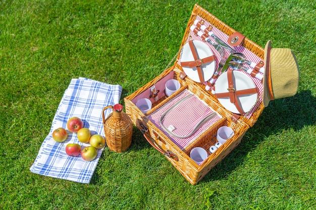 Корзина для пикника на зеленой солнечной лужайке в парке