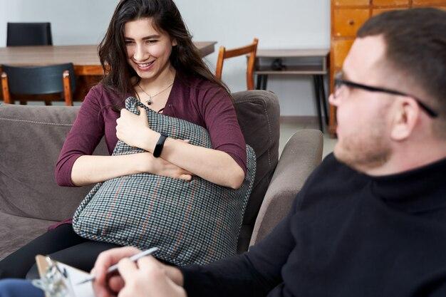 自宅のプライベートオフィスでメモを書いている彼女のセラピストと話している女性患者