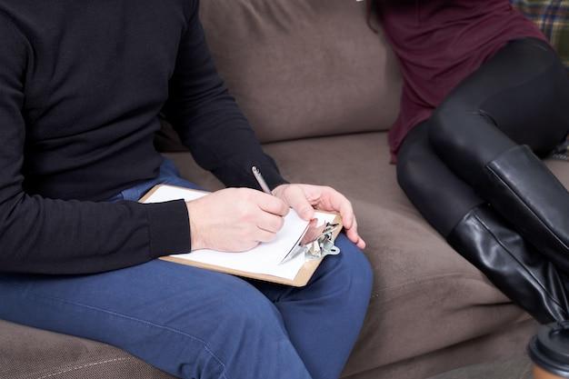 ノートを作っている彼女のセラピストと話しているトリミングされた女性患者