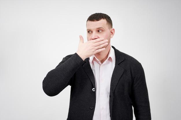 Портрет человека с рукой над его ртом, глядя в сторону, ошеломлен и потерял дар речи