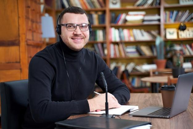 Мужской блоггер потокового из библиотеки, используя ноутбук и микрофон