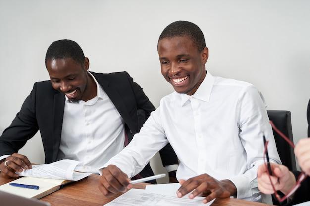 オフィスのテーブルで同僚と事務処理を議論するアフリカ系アメリカ人のビジネスマンを笑ってください。