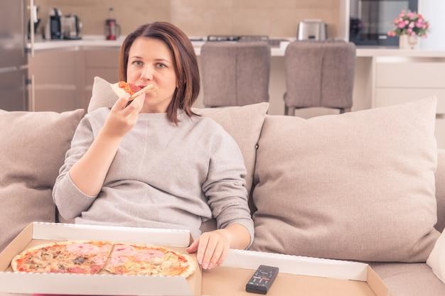 Удивленная женщина ест пиццу и смотрит телевизор с пультом у себя дома, теплые тона