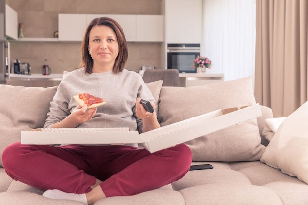 Красивая женщина ест пиццу и смотрит телевизор, держа пульт дистанционного управления дома, оранжевый тон