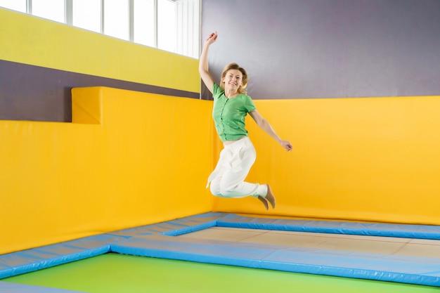 Молодая женщина прыгает на батуте в спортивном центре