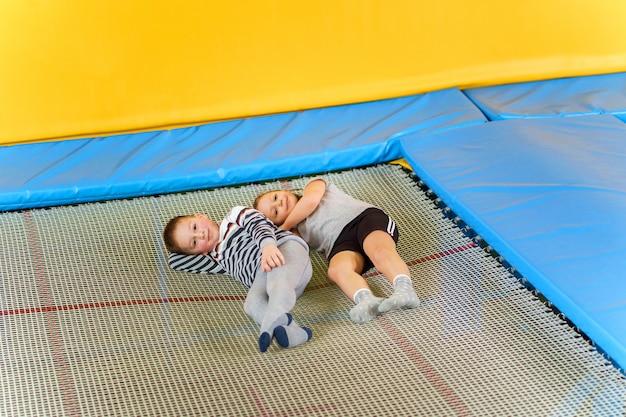Счастливые улыбающиеся маленькие дети, лежа на батуте в развлекательном центре