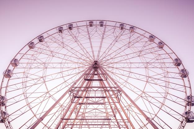 Силуэт колеса обозрения на фоне голубого неба