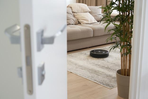 Робот пылесос на полу в уютной современной гостиной, вид через открытую дверь