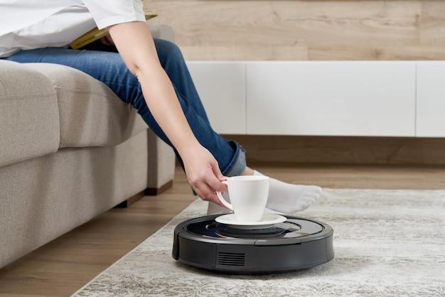 彼女がソファーで休んでいる間に女性に一杯のコーヒーをもたらすロボット掃除機