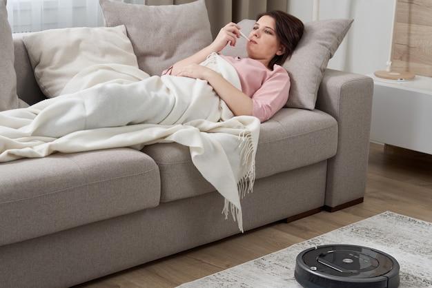 ロボット掃除機がリビングルームのカーペットを掃除している間、ソファーに横になっているインフルエンザを持つ女性