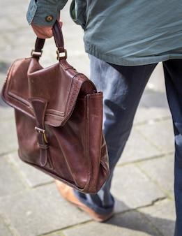 仕事に行くカジュアルな革のブリーフケースを持って男のクローズアップ