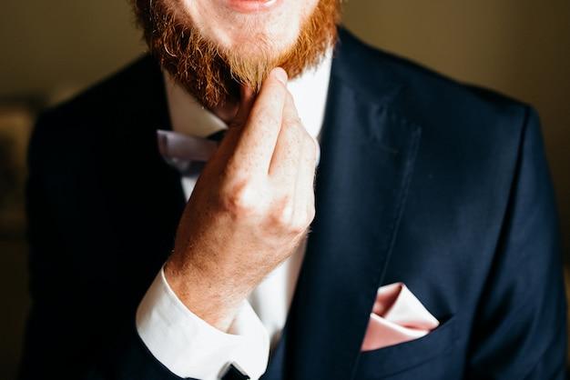 彼の赤いひげに触れるひげを生やした男