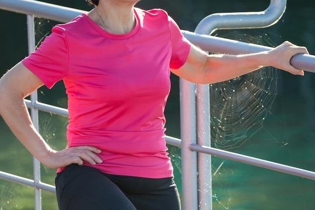 背景にクモの網とビーチの桟橋で屋外演習を行うスポーティなフィットネス女性