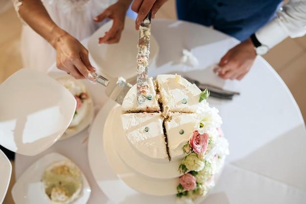 新郎新婦が結婚披露宴でスタイリッシュなウェディングケーキを切る