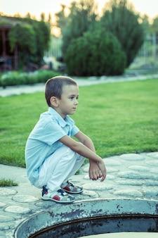 悲しい少年が一人で通りに座っている、不幸な孤独な子供、青いトーン