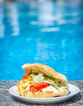 スイミングプールのそばのプレートに新鮮なサンドイッチ