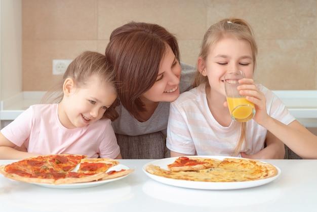 Мать и две дочери едят домашнюю пиццу за столом на кухне, концепция счастливой семьи