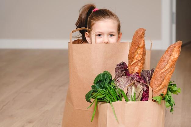 野菜とパン、コピースペースと食料品を隠して紙袋に座っている小さな女の子
