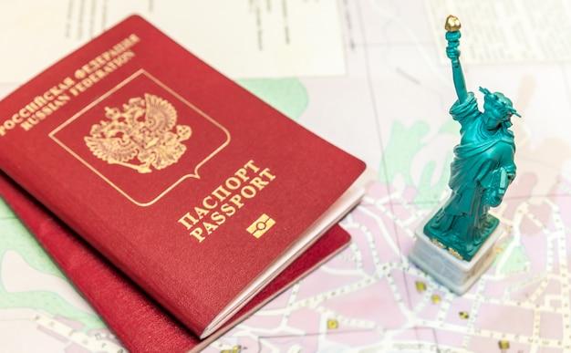 自由の女神像と地図上のロシアの国際パスポートは、旅行、休暇を象徴します