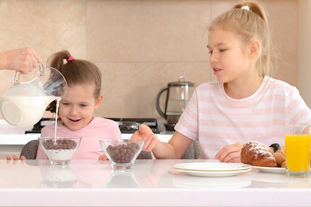 Мать, где подают завтрак для двух своих дочерей за столом на кухне, концепция счастливой матери-одиночки