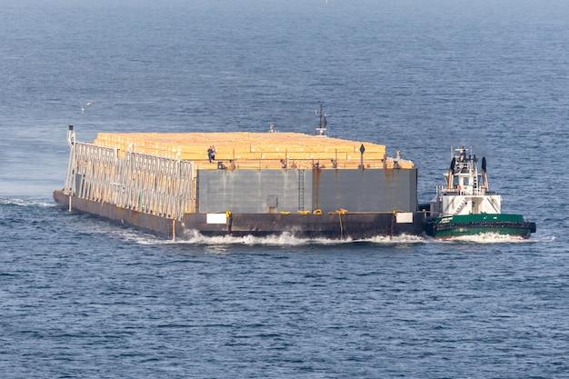 デッキに木材貨物が積まれたばら積み貨物船
