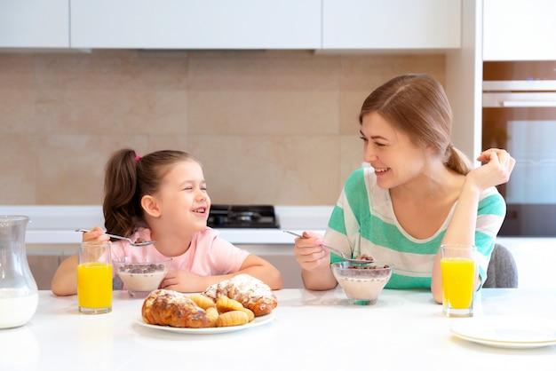 幸せなシングルマザーコンセプトキッチンのテーブルで彼女の娘と一緒に朝食を持つ母