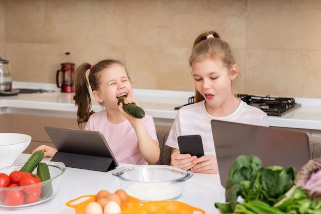 キュウリを食べるとキッチンのテーブルでタブレットを使用して小さな女の子
