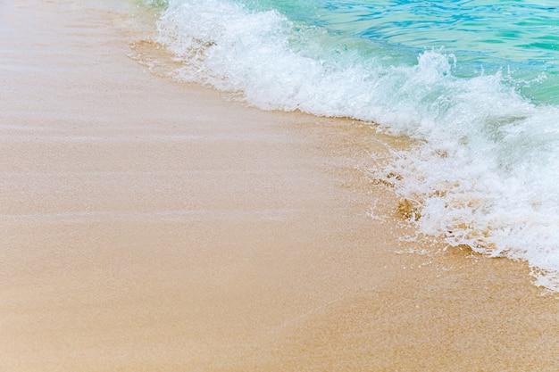 砂浜、背景に柔らかい青い海の波