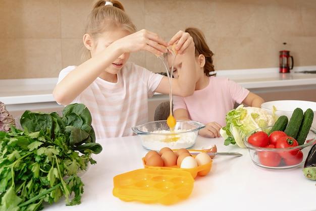 Счастливые семьи веселые дети готовят тесто, пекут печенье на кухне. сестры весело смеются