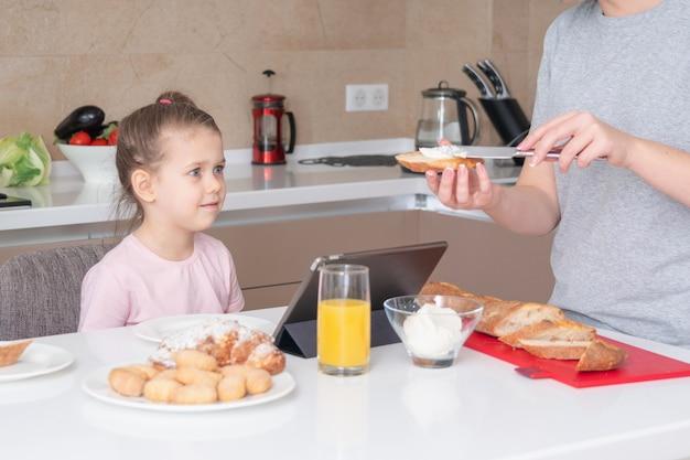 Мать делает ее дочь бутерброд на завтрак