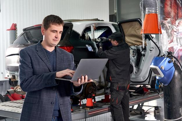 メカニックが背景に車を修理する自動車修理店で車の近くに立っている間ラップトップを保持しているマネージャー
