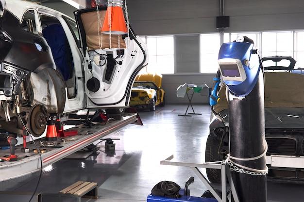 Сварочное оборудование в автосервисе, шлем висит на бензобаке, людей нет