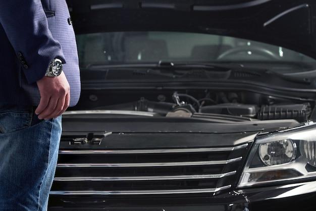 フードが開いている車のエンジンを探している男性