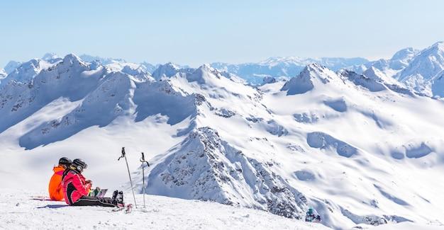 Две девушки сидят высоко в горах