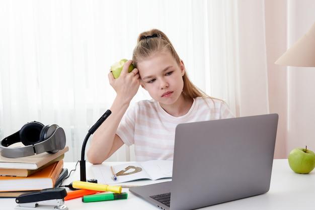 Девочка-подросток учится с помощью видеоконференции, электронного обучения с учителем и одноклассниками на компьютере у себя дома. обучение на дому и дистанционное обучение, концепция онлайн-образования