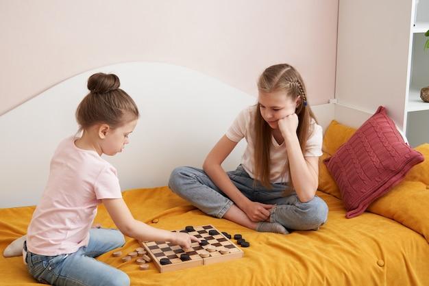 Две сестры играют в шашки на плохом развлекаться дома, концепция счастливых детей