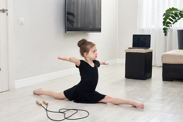 Маленькая девочка, делающая гимнастику, тренируется дома, используя онлайн-обучение с ноутбуком, концепцию интернет-образования
