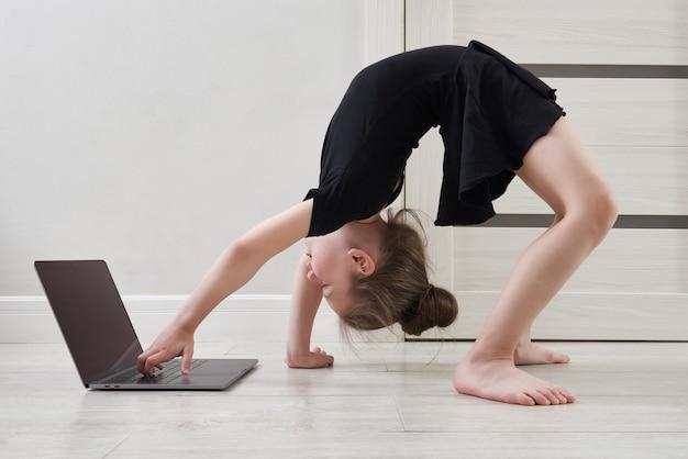 ラップトップコンピューター、インターネット教育の概念とオンライン学習を使用して自宅で体操をしている女の子