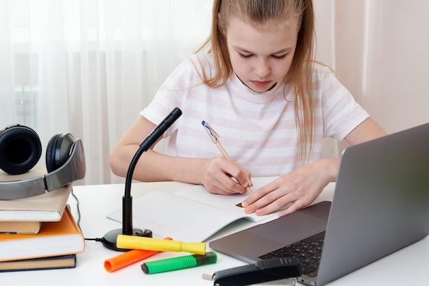 Портрет девочки-подростка, учащейся онлайн с наушниками и ноутбуком, делающим заметки в тетради, сидящей за ее столом дома, делающей домашнюю работу