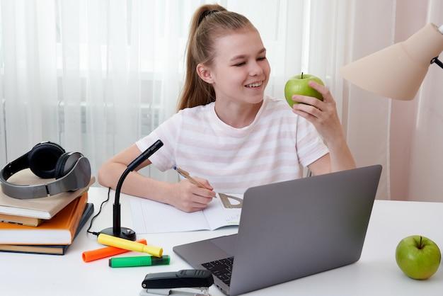 Девочка-подросток держит зеленое яблоко учится у себя дома с ноутбуком