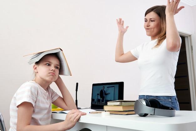 母と娘が宿題について戦って、怒って母親は少し退屈な娘、ホームスクーリング、誤解に怒っています