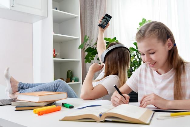 Мать не помогает дочери делать домашнее задание, используя ее смартфон и слушая музыку в наушниках