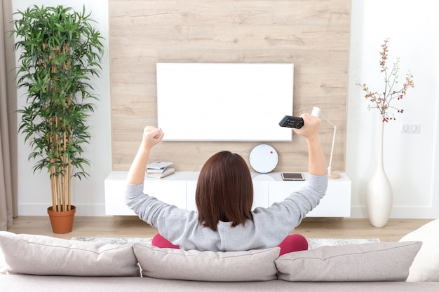 Молодая счастливая женщина смотрит возбужденный телевизионный футбольный спортивный матч или телевизионный конкурс
