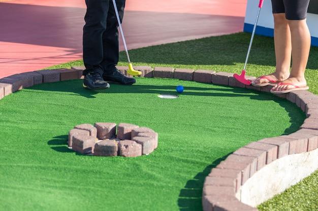 男はミニゴルフゲーム中にボールを打つために準備します